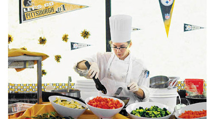 Ashley Moyer, 21, prepares to cook lunch for the Steelers at St. Vincent College.