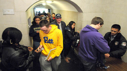 The line snakes out the door as security officers check photo IDs and examine bags in April at the Cathedral of Learning ground floor entrance along Bigelow Blvd. Increased security procedures took effect in the wake of multiple bomb threats on campus.