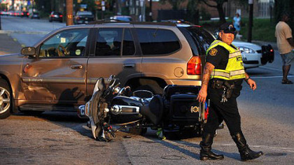 Police direct traffic around the scene of an accident involving an officer riding a motorcycle on Penn Avenue at its intersection with North Lexington.