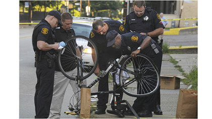 Police officers examine the bike belonging to James Price of Homewood, who was struck and killed by a hit-and-run driver on Penn Avenue early Wednesday.