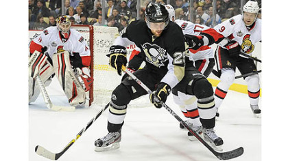 Penguins Eric Tangradi battles for loose puck against the Senators.