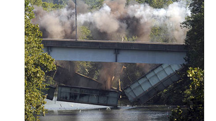 Structural steel from the 31st Street Bridge plunges into the back channel of the Allegheny River at Washington's Landing during a controlled explosion Thursday morning. The north end of the bridge will be rebuilt to incorporate a new interchange with Route 28.