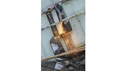 A worker puts the cutting torch to structural steel from the 31st Street Bridge after a controlled explosion.
