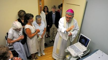 Bishop David Zubik blesses the ultrasound machine Thursday at the North Side office of Women's Choice Network.