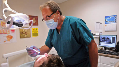 Dentist Rick Bennett, a volunteer, sees a patient at the Community Health Clinic of Butler County.