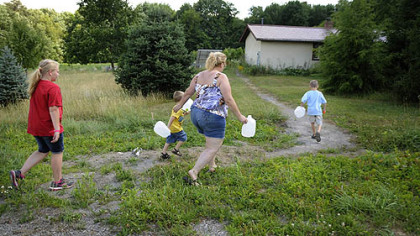 Shelley Carlson, 42, center, walks to fill up gallon water jugs behind a Lutheran church camp several miles from her home in the Woodlands in June. A family friend, Kayla Zeidler, 10, left and two of Ms. Carlson&#039;s three sons, Dylan, 3, and Logan, 6, race to help her.  Ms. Carlson noticed an odor and discoloration in her tap water in January 2011.