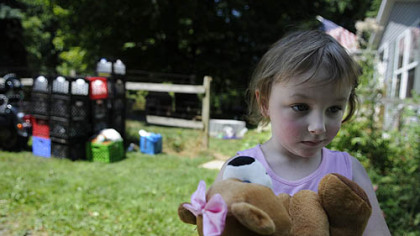 Skylar Sowatsky, 3, stands outside her home in the Woodlands on moving day. Skylar, her mother, Kim McEvoy, and father, Peter Sowatsky, moved out of the area after living without water since the winter of 2011. &quot;Once you lose water, basic human needs are all that matter. I feel like I can relate to people on the other side of the world living without water,&quot; Ms. McEvoy said.