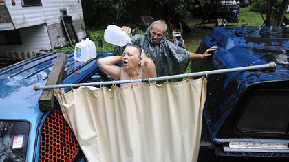 Fred McIntyre, 56, helps his wife Janet, 52, shower during a heavy rainstorm July 19.  The McIntyres usually drive 11 miles to their son&#039;s home to shower but when the weather is nice, they will set up a makeshift shower in their front yard in the Woodlands.