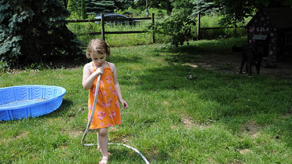 Skylar Sowatsky, 3, plays with a garden house outside of her home on May 29.  Skylar&#039;s mother, Kim McEvoy has moved them out of the Woodlands because they have no water at their home.