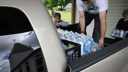 Volunteers Jason Bell and Diane Fipe load water into a pickup truck while water delivery coordinator Janet McIntyre counts up the gallons June 4 at White Oaks Springs Presbyterian Church near Evans City.