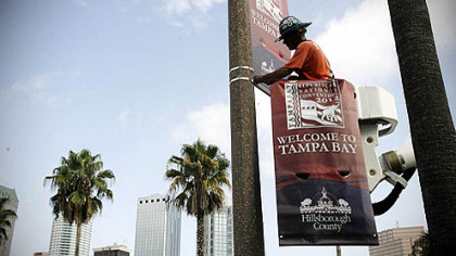 A worker begins installing banners for the Republican National Convention in front of the Tampa Bay Times Forum, in Tampa, Fla.