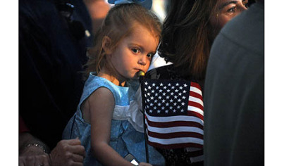 A girl holds an American flag during a rally for Paul Ryan today.