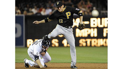 the Pirates&#039; Clint Barmes jumps over the Padres&#039; Yasmani Grandal as he turns a double play during the third inning.
