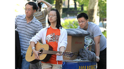 Victoria Lang strums her brother's guitar as she helps  during move-in day Tuesday at the University of Pittsburgh. Kevin Lang, right, a sophomore majoring in finance, was getting help also from father, Zig. The Lang family is from Collegeville, Pa.