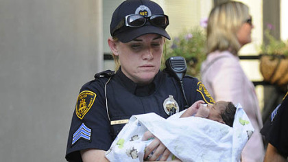 Three-day-old Bryce Coleman is carried to an ambulance by Pittsburgh police Sgt. Cristyn Zett.