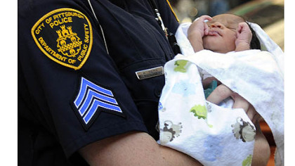 Three-day-old Bryce Coleman is carried to an ambulance by a Pittsburgh police officer Thursday evening.