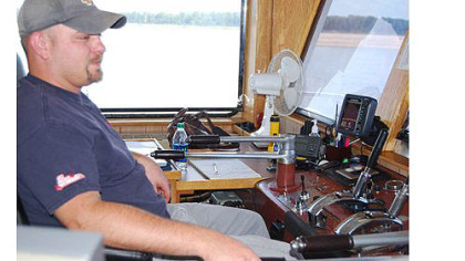 Sam Lynch, a tow boat pilot in training, at the helm of the Captain Gerald Boggs on the Mississippi River.