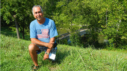 "Gary Hooper of Jefferson, Md., kneels near Burnside Bridge, Antietam Battlefield. His great-great-grandfather, Abraham Burns, had served with the 52nd Virginia Infantry. That unit, part of ""Stonewall"" Jackson's command, had fought the Union troops trying to capture the West Woods. ""I still have his bayonet,"" Mr. Hooper said."