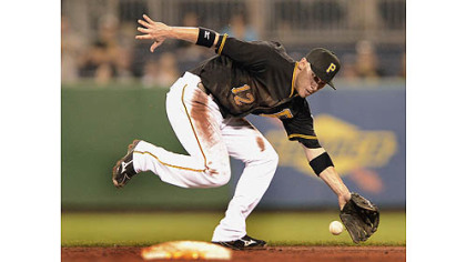 Pirates shortstop Clint Barmes can not catch up to a ball hit up the middle by the Cardinals starting pitcher Kyle Lohse for a single.