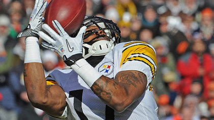 The Steelers' Mike Wallace, hauling in pass from Ben Roethlisberger for a touchdown in 2011, is back in camp.