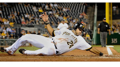 The Pirates&#039; Pedro Alvarez reaches out to touch home as he slides safely past Cardinals catcher Tony Cruz.