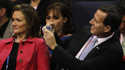 Former Pennsylvania Sen. Rick  takes a picture on Tuesday of his wife Karen during the convention.