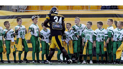 The Steelers' Rashard Mendenhall greets youth football players tonight before the start of the game against the Panthers.