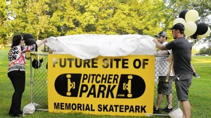 Mary Pitcher and her sons, Jonathan, right, and Brady, unveil a sign in Carnegie Park, the future site of Pitcher Park, a skate park named in honor of the two sons she lost in a drowning accident in 2008.