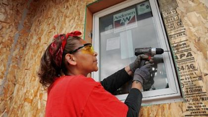 Nakeia Dismond, an Eco-Village home owner, helps install the first window in her River Falls, Wis., home.The energy-saving window is one of many energy-efficient features used in Eco-Village, a Habitat for Humanity project.