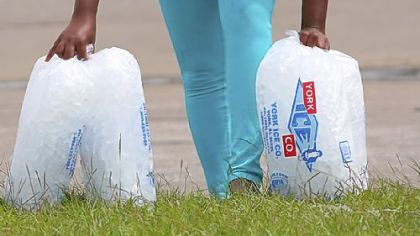 A woman pauses Friday while carrying bags of ice from an aid distribution center in New Orleans for victims of Isaac. The center was one of three in the city operated by the Louisiana National Guard to assist residents, many of whom still have no electricity because of the storm.