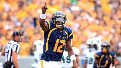 West Virginia University quarterback Geno Smith celebrates a touchdown pass against Marshall during today's game in Morgantown.