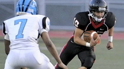 Upper St. Clair quarterback Pete Coughlin runs against Woodland Hills' Daechaud Ausbrooks in the first half Friday Upper St. Clair High School.