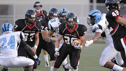 Upper St. Clair runningback Gabe Boyd rolls through Woodland Hills' defense.