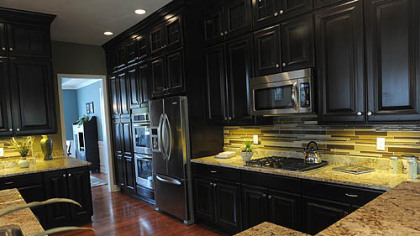 The kitchen has custom maple cabinetry topped by decorative glass-doored cabinets.