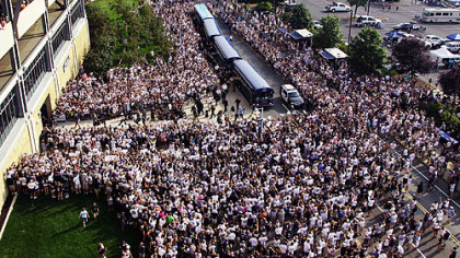 Penn State fans surround the football team as the players arrive by bus at Beaver Stadium for Saturday's season opener against Ohio University.
