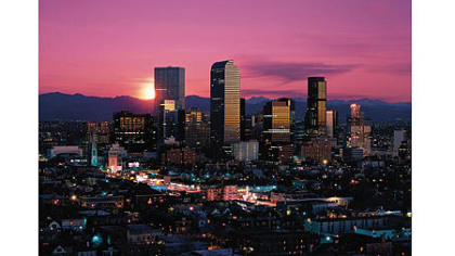 The skyline of Denver against the Rocky Mountains.