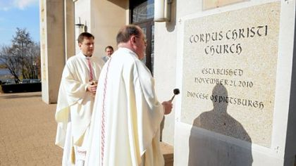 In this November 2010 photo, the Rev. Frederick L. Cain, regional vicar, right, and the Rev. Stephen Kresak use a holy water sprinkler to bless the cornerstone of Corpus Christi Church in McKeesport.