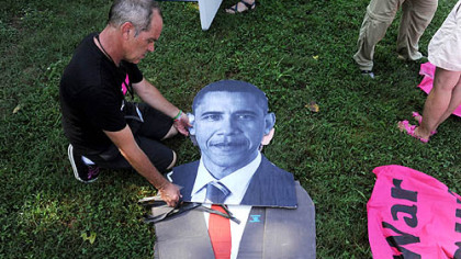 Tighe Barry of Los Angeles creates a cutout of President Barack Obama for the March on Wall Street South protest before the start of the Democratic National Convention in Charlotte, N.C., on Sunday.