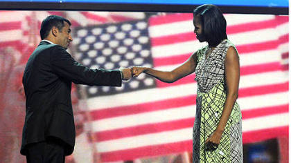 Actor Kal Penn, left,  jabs fists with first lady Michelle Obama during an interview at the Time Warner Cable Arena before the official start of the Democratic National Convention in Charlotte.