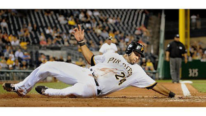 Pedro Alvarez reaches out to touch home as he slides safely past St. Louis catcher Tony Cruz.