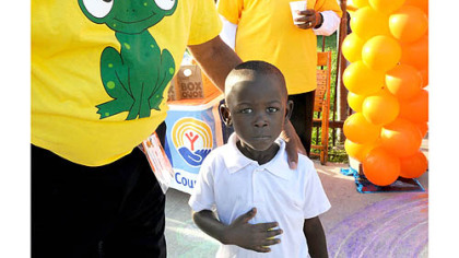 Four-year-old Pithas Pierre is greeted for his first day of kindergarten at Weil Elementary in the Hill District today.