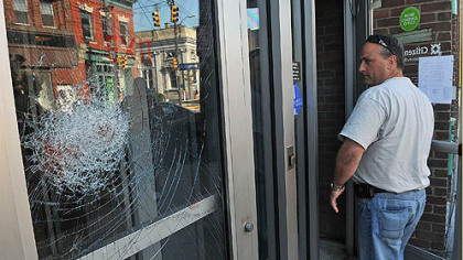 A Pittsburgh police officer looks at the shattered door of the Citizens Bank on Butler Street in Lawrenceville after a Thursday morning robbery attempt.