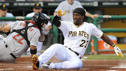 Andrew McCutchen slides safely past Astros catcher Carlos Corporan in the first inning Wednesday night at PNC Park.