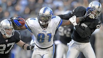 Calvin Johnson and Megatron: One and the same? Has anyone ever seen them in the same place? Here the Detroit Lions wide receiver stiff-arms Oakland Raiders cornerback DeMarcus Van Dyke (23) as defensive back Matt Giordano (27) approaches during a game last year in Oakland.