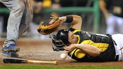 Catcher Rod Barajas hits the dirt missing the throw from first basemen Gabby Sanchez as the Cubs' Brett Jackson scores Friday night at PNC Park.