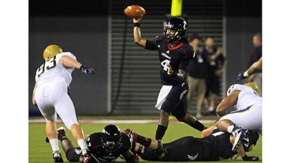Cincinnati quarterback Munchie Legaux (4) passes against Pittsburgh in the first half.