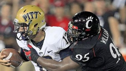 Pitt quarterback Tino Sunseri, left, is sacked by defensive lineman John Williams in the first half Thursday in Cincinnati.