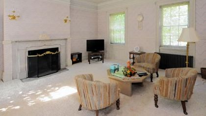 The living room features a pair of electric candelabras and white wainscoting.
