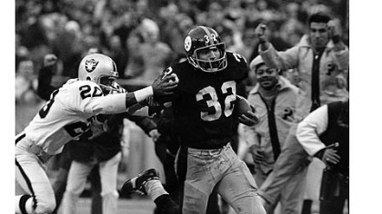 "The Steelers' Franco Harris, right, eludes a tackle attempt by the Raiders' Jimmy Warren on the way to scoring on a play known as the ""Immaculate Reception."""