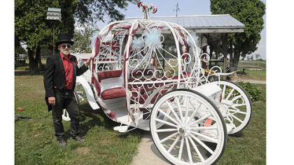 Bill Wolfe of Apollo stands in front of a carriage used mostly for weddings at his horse-drawn carriage business, which supplies carriages for a variety of occasions.
